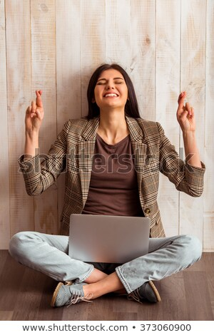 Smiling female entrepreneur with her fingers crossed against a white background stock photo © wavebreak_media