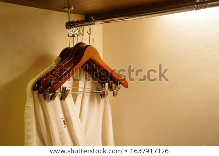 White robes with wooden hangers in hotel wardrobe Stock photo © punsayaporn