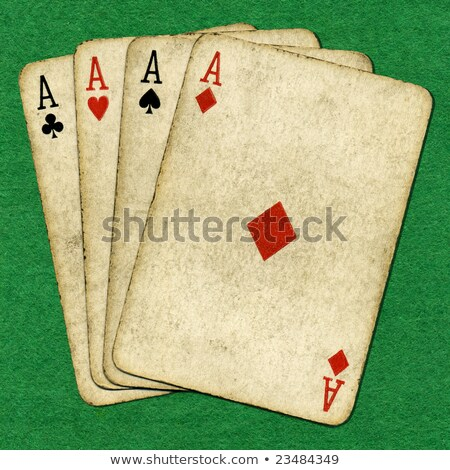 Four old vintage dirty aces poker cards on a green cloth. Stock photo © latent