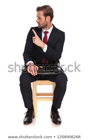 Attractive young fashion man sitting on a chair while Stock photo © feedough