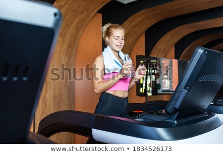 Young sportswoman walking on treadmill and drinking water in gym  Stock photo © deandrobot