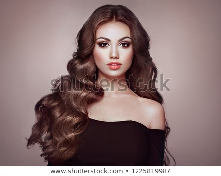 Elegant girl model with brown long wavy hair in black dress sitt Stock photo © Victoria_Andreas