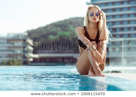 Beautiful young girl in blue swimsuit posing outdoors Stock photo © deandrobot