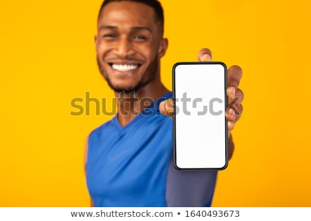 Smiling young sportsman using blank screen mobile phone on armband Stock photo © deandrobot