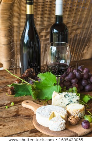 Grape, cheese,  with a one glass of red  wine on green backgroun Stock photo © Yatsenko