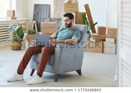 portrait of smiling young bearded man sitting with laptop stock photo © deandrobot
