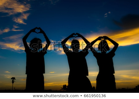 group standing on grass in heart shape stock photo © is2