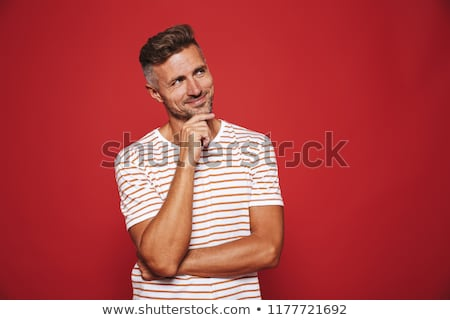 Unshaved man in striped t-shirt touching chin and looking aside  Stock photo © deandrobot