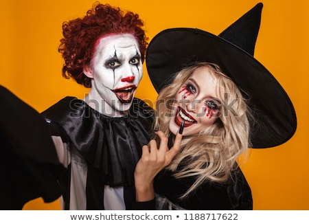 Image of witch woman and joker man wearing black costume and hal Stock photo © deandrobot