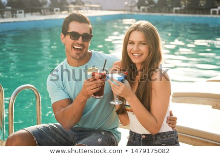 young couple with glasses of alcohol cocktails near swimming poo stock photo © dashapetrenko