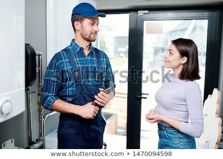 Young casual housewife looking at technician or plumber Stock photo © pressmaster