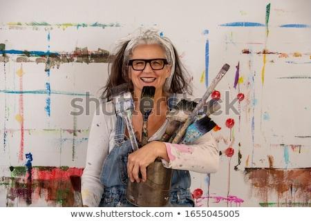 portrait of senior woman in glasses brushing hair Stock photo © dolgachov