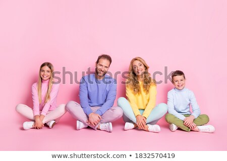 Photo of cheerful girl and daughter sit crossed legs on floor, hold paint rollers, paint room in whi Stock photo © vkstudio