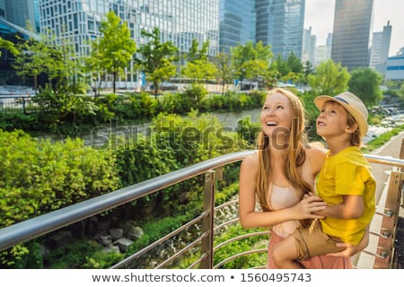 Mom and son tourists on the background of a waterfall. Traveling with kids concept. What to do with  Stock photo © galitskaya