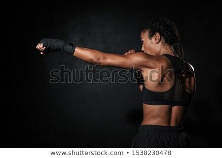 Image of feminine woman wearing sportswear training in boxing hand wraps Stock photo © deandrobot