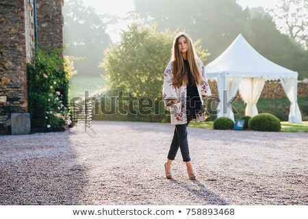 Portrait of pleasant looking slim tall woman wears cape and high heeled shoes, stands crossed legs,  Stock photo © vkstudio
