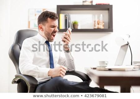 Enojado empresario teléfono teléfono celular aislado Foto stock © lisafx
