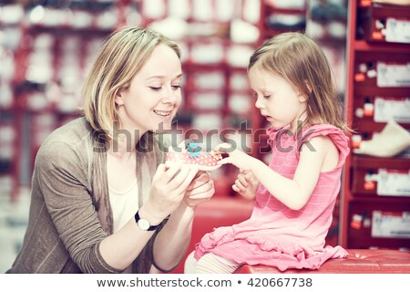 Mother with daughter choose footwear in shop Stock photo © Paha_L