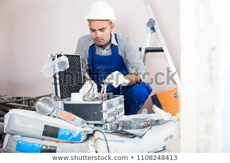 Workman sitting on a toolbox with notebook Stock photo © photography33