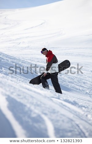 Snowboarder walking up a mountainside Stock photo © photography33