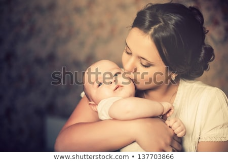 Stock photo: Happy Young Mother Kissing A Baby