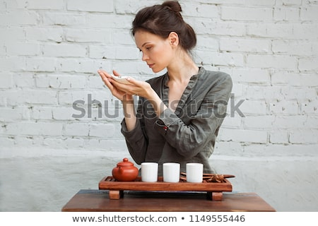 young woman sitting in meditation pose in front of tea set and a stock photo © hasloo