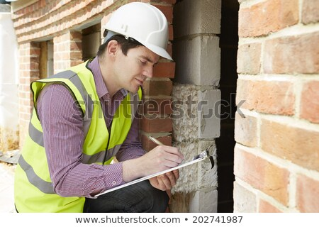 Foto stock: Architect Checking Insulation During House Construction