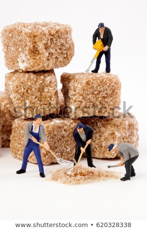 Stock photo: Miniature worker working on a sugar cube