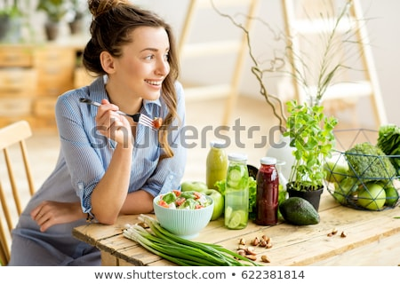 happy beautiful smiling woman eating healthy salad stock photo © deandrobot