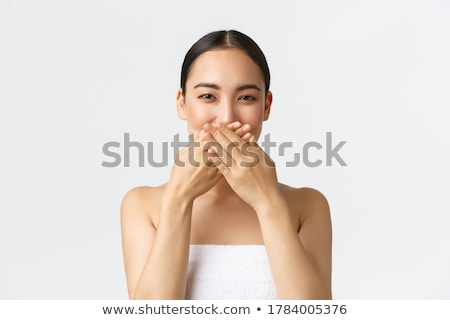 smiling woman in towel covering eyes with hands stock photo © deandrobot