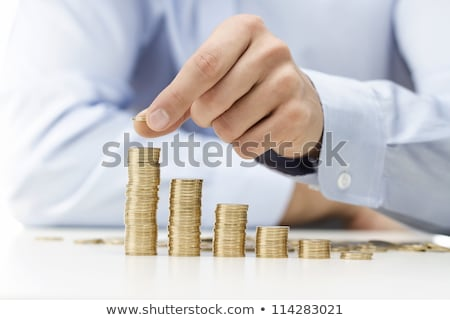 male hand stacking gold coins into increasing columns stock photo © vlad_star