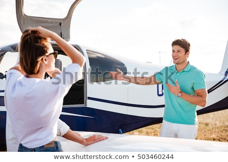 Pilot inviting passengers on board of private airplane Stock photo © deandrobot
