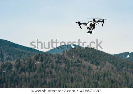 drone with camera hovering over mountains stock photo © homydesign