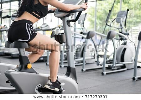 young woman riding stationary bicycle stock photo © rastudio