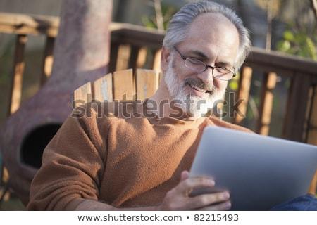 Boomer Reading On Tablet Computer Stockfoto © EdBockStock