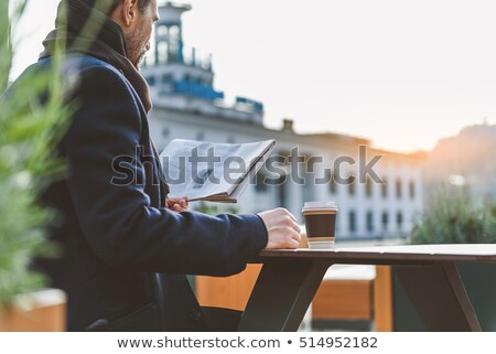 senior man with coffee reading newspaper outdoors stock photo © dolgachov