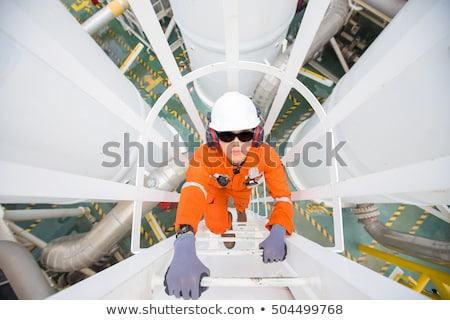 Worker climbing ladder on oil rig Stock photo © IS2