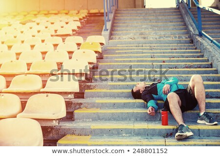 Tired sportsman finished running at the stadium Stock photo © deandrobot