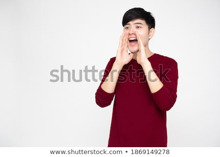excited screaming shocked young asian man standing isolated over yellow background using laptop comp stock photo © deandrobot