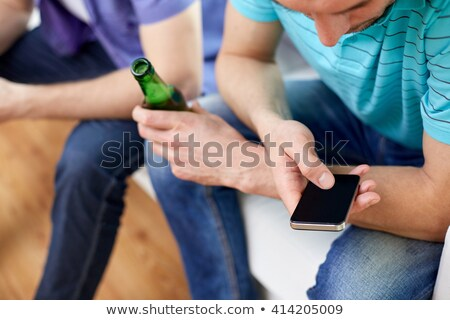 close up of man with smartphone and beer bottle Stock photo © dolgachov