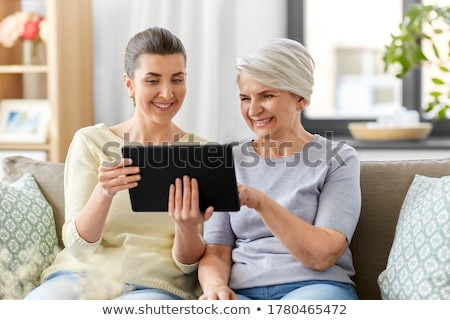 happy senior woman with tablet pc at home stock photo © dolgachov