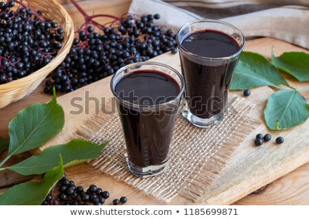 Stock photo: Two glasses of elderberry syrup on a wooden table