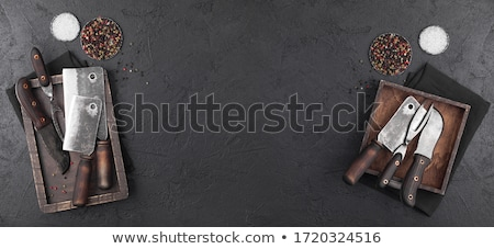 Wooden menu board and vintage meat knife and fork on kitchen towel and black stone table background. stock photo © DenisMArt