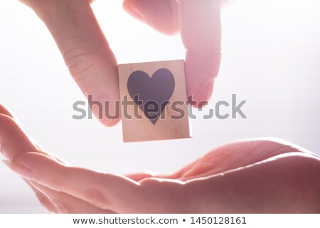 Male Hand Giving Wooden Block With Heart Shape To Female Stock photo © AndreyPopov