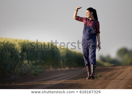 Happy, satisfied young woman standing in the wheat field. Stock photo © Lopolo