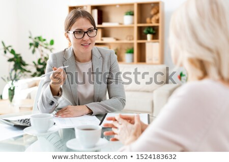 Confident young auditor with pen sitting in front of client and consulting her Stock photo © pressmaster