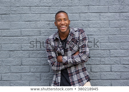 portrait of african young man crossing arms and smiling stock photo © diego_cervo