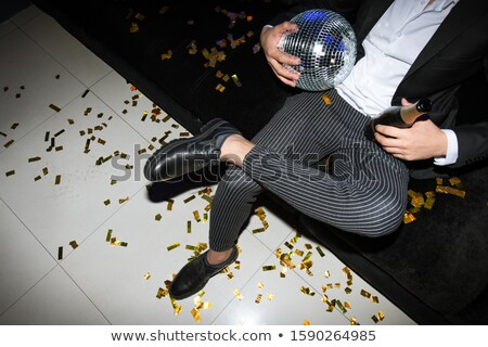 Legs of elegant man with disco ball and bottle of champagne relaxing on couch Stock photo © pressmaster