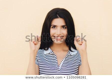 Headshot of happy brunette female model clenches fists, hopes for something good, has broad smile wi Stock photo © vkstudio
