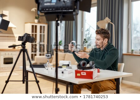 male blogger with earphones videoblogging at home stock photo © dolgachov